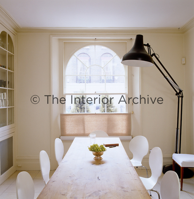 A larger than life angle poise floor lamp standing in the corner of this bright dining room