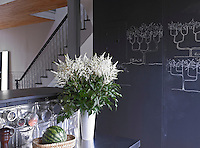 The blackboard, used for shopping lists and inspirational drawings, doubles as a sliding door for the cupboard it conceals
