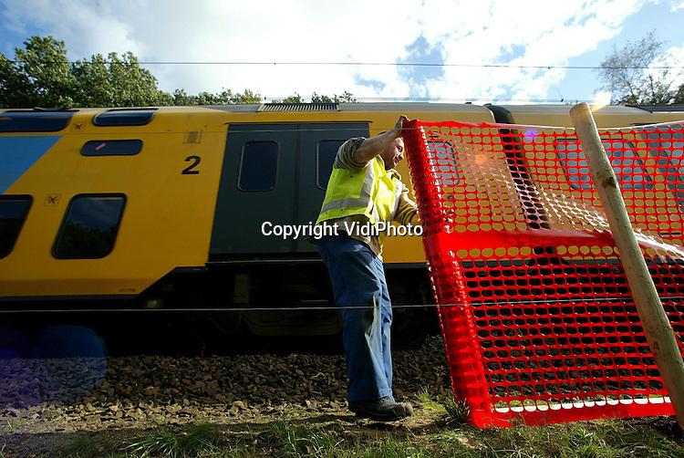 Foto: VidiPhoto..RHENEN - De NS plaatst op dit moment een zestal plaatsen in Midden-Nederland als proef plastic netten langs de rails. ..Daarmee moet worden voorkomen dat natte bladeren op de rails het treinverkeer vertragen. Vooral in de buurt van stations, zoals hier bij Rhenen, wordt er vaak flink geremd. Door natte bladeren verliezen de wielen hun grip op het ijzer. Het pilot-project, dat dit jaar voor het eerst wordt uitgeprobeerd in bosrijke gebieden, moet uitwijzen of netten de oplossing zijn voor het probleem. Uitvoerder van het project is Hooijer Renkum BV Grond- en Wegenbouw.