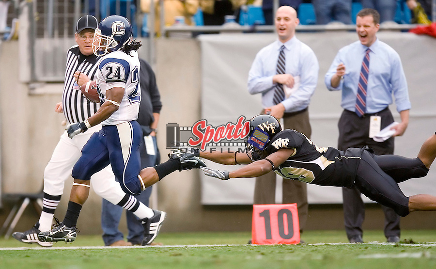 Connecticut wide receiver Larry Taylor (24) avoids the diving tackle attempt of Wake Forest cornerback Kerry Major (29) as he returns a punt 68 yards for a touchdown at the Meineke Car Care Bowl Saturday, December 29, 2007 in Charlotte, NC.