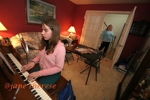 Julianne Salem 13 of Telford, Pa., practices the piano as her mother Lisa watches on a cold Thursday March 2, 2006. Three of the Salem children play musical instruments. Sam the trombone, Jake the guitar and Julianne the piano. The Salem children, 3 sets of twins, are from Nevel, Russia. Sophia and twin Joseph were adopted at 11 months of age by Hythem and his wife Lisa. The other twins, Selene and Julianne 13 along with Sam and Jake, were adopted just 20 months ago. All children are thriving in school, socially and physically. photo by jane therese