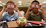 pvcKALEID2/9-27-06/RR. Bobby Ashe (CQ), left, and Justin Martinez (CQ), right, both age 10, and both 5th graders at Martin Luther King Jr. Elementary School in Rio Rancho, cover their eyes with opaque plastic cups while learning about kaleidoscopes through an Explora educational program, photographed Wednesday Sept. 27, 2006.  During the kaleidoscope seminar, students at the school learned about such things as the properties of mirrors, light, and lenses and got a chance to make their own kaleidoscopes.  (Pat Vasquez-Cunningham/Journal)