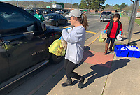 Lori Gaither (center), a literacy aide at Greenland Elementary School, and Lydia Velasco, an ESL aide, distribute bags Saturday, March 21, 2020, during a giveaway of food and household items at the school. The school, along with Lincoln, Gravette and Pea Ridge, partners with Essentials Outreach and Tyson Foods to provide necessary items to families in its district on third Saturday of the month. After serving 27 families in its first month last month, Greenland gave items to 271 individuals on Saturday. Visit nwaonline.com/200322Daily/ for today's photo gallery.<br /> (NWA Democrat-Gazette/Andy Shupe)