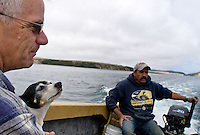 Kevin Lunny, owner of Drakes Bay Oyster Company (left), holds his pet rat terrier, Pippin, on a boat ride out to the main oyster cultivation area in lateral channels of Drakes Estero near Drakes Bay Oyster Company in Inverness, Calif., on August 30, 2012. (Alvin Jornada / Special to The Chronicle)