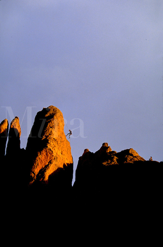 Distant view of the silhouette of a rock climber as he approaches to top of a rock formation. Smith Rock State Park, Oregon.