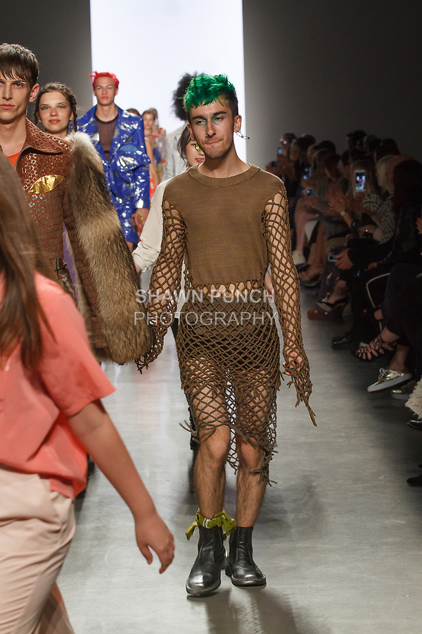 Graduating design student Alex Mangus, walks runway with model at the close of 2017 Pratt fashion show on May 4, 2017 at Spring Studios in New York City.