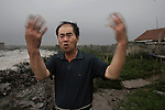 "A salt-field worker expresses his complaints with great anger in Lianyungang City: ""I can't bear any longer the pungent smell of the gas from the chemical factories when the wind blows."" Jiangsu Province. July 19, 2008."