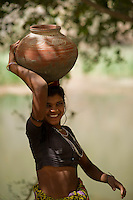 A young girl fills water in an earthen pot rom the river.
