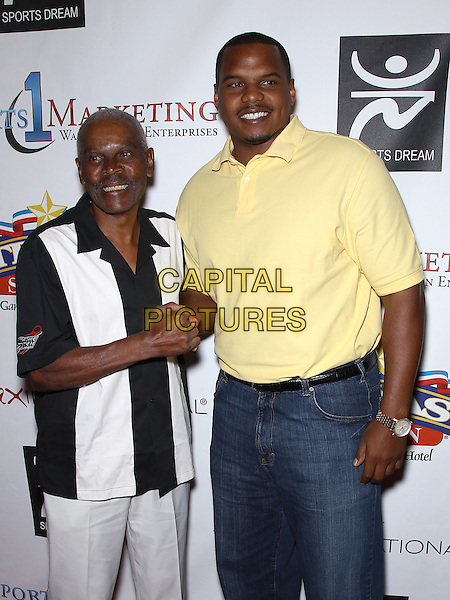 Marlin Briscoe, Chester Pitts.Warren Moon hosts The Eleventh Annual Sports Dream Bowl Benefit in Las Vegas at Texas Station, Las Vegas, Nevada, USA..June 25th, 2011 .half length black white stripe shirt yellow top shaking hands.CAP/ADM/MJT.© MJT/AdMedia/Capital Pictures.