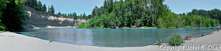 Panorama of Lower Elwha River section with cliffs near mouth of river by Elwha Tribal Reservation, with figure of National Park Service fisheries scientist on shore. Washington State.