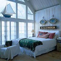 An antique optician's sign hangs above the bed and a large model boat sits on a shelf above the floor-to-ceiling windows in the gallery master bedroom
