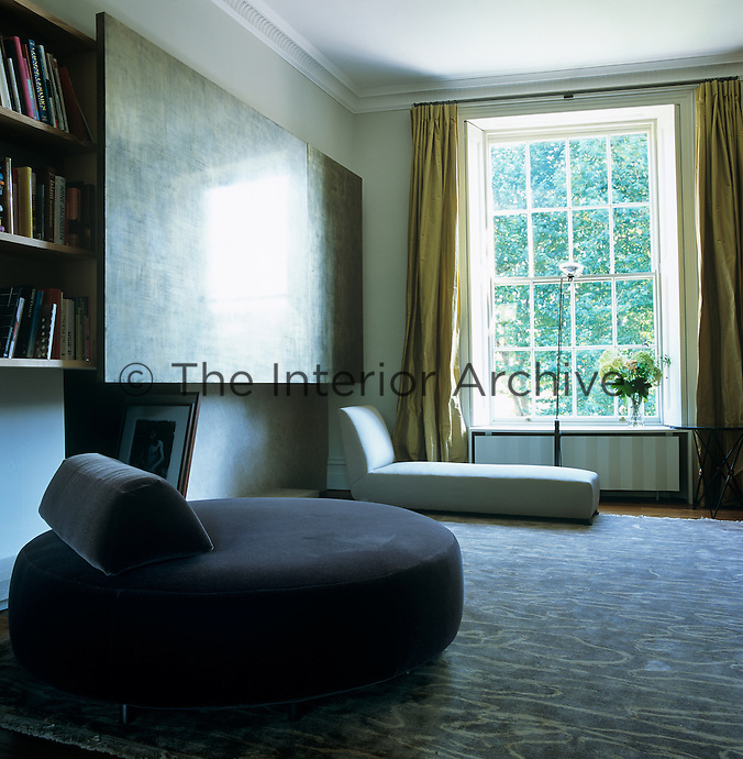 The circular sofa in the library is designed by Eric Gizard and the painting by Jerome Mazeret inspired the colour scheme of the room