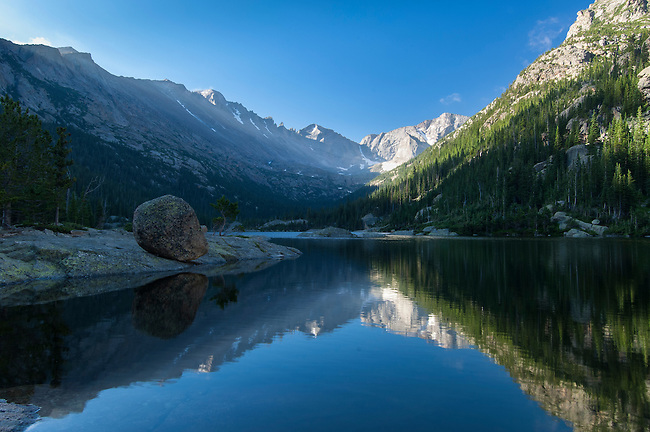 On a summer morning, mountain peaks are reflected on calm water of Mills Lake, subalpine life zone in Glacier Gorge, Rocky Mountain National Park, Colorado, USA