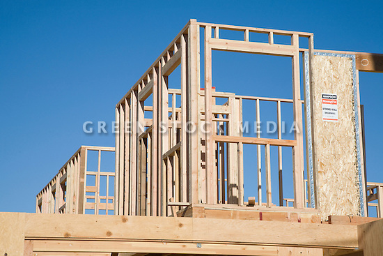 The skeletal wood frame walls of the second-story of a residential home rises into a blue sky.