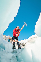 A glacier guide makes way and guides group of tourists through ice formations on the Franz Josef Glacier - Westland National Park, West Coast, New Zealand