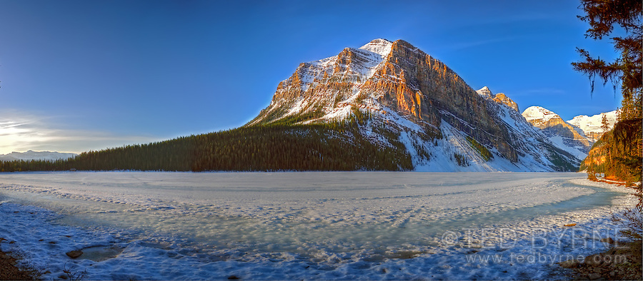 Panoramic image of golden sunrise on frozen Lake Louise and surrounding mountains.
