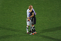 Jay DeMerit hugs USA goalkeeper Tim Howard after their defeat by Ghana. Ghana defeated the USA 2-1 in overtime in the 2010 FIFA World Cup at Royal Bafokeng Stadium in Rustenburg, South Africa on June 26, 2010.