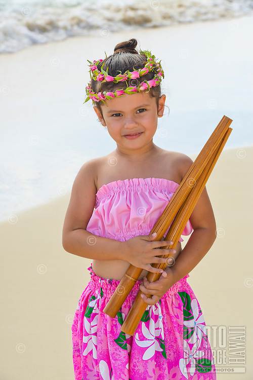 A young local girl wearing a rose lei holds pu'ili (split bamboo percussion sticks used as hula implements) on Lanikai Beach in Kailua, Windward O'ahu.