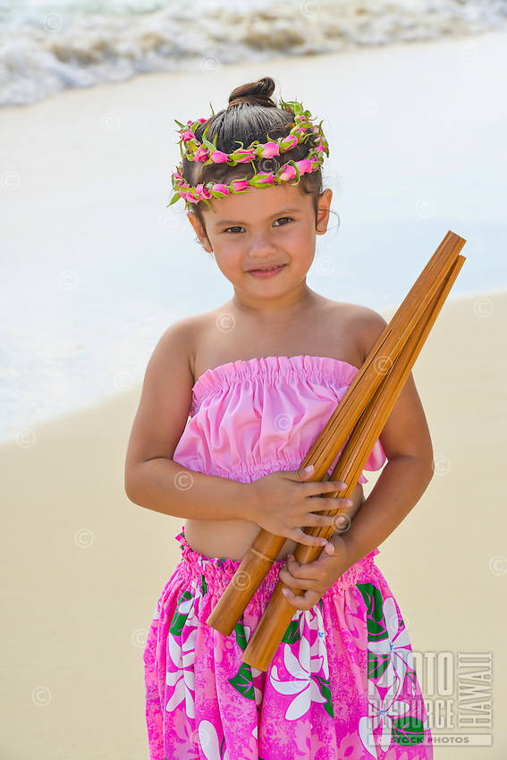 A young local girl wearing a rose lei holds pu'ili (split bamboo percussion sticks used as hula implements) on Lanikai Beach in Kailua, Windward O'ahu.