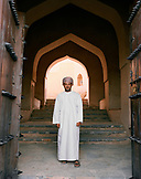OMAN, man in traditional clothing standing in front of steps, portrait