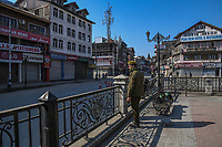 A security officer guards a building in the deserted Lal Chowk area. The first positive case of coronavirus was identified in the Khaniyar area the previous night leading the local government to impose section 144 in Kashmir to stop spread of Coronavirus.