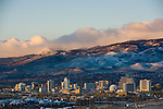 Stormy Reno sunrise over downtown with snowy mountains.
