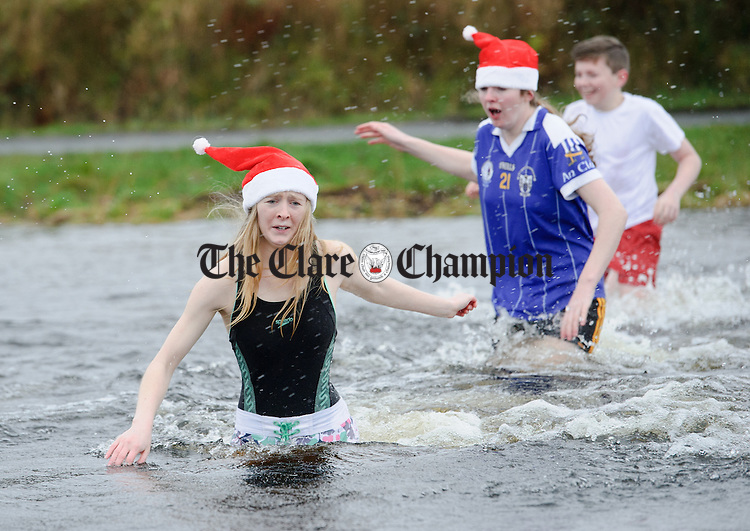 Sisters Aisling and Sinead Reidy enter the freezing water during the annual Christmas day swim at Gortglas  Lake, Kildysart in aid of the West Clare Mini Marathon Cancer fund. Photograph by John Kelly.