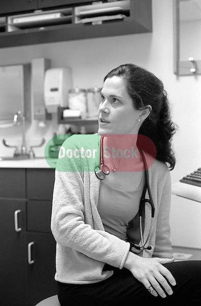 Young female internal medicine resident physician seated in examination room speaking with patient off camera
