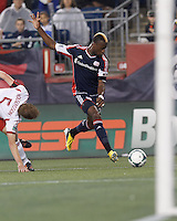 New England Revolution forward Dimitry Imbongo (92) crosses the ball. In a Major League Soccer (MLS) match, the New England Revolution (blue) tied New York Red Bulls (white), 1-1, at Gillette Stadium on May 11, 2013.