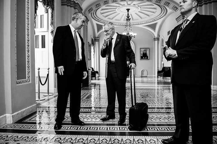 Incoming Senate Majority Leader McConnell's spokesman Don Stewart, left, speaks with outgoing Senate Majority Leader Harry Reid, D-Nev., as Reid leaves the Capitol for a meeting at the White House with Congressional leaders, three days after the GOP election victory.