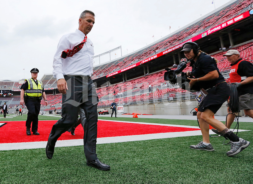An ESPN camera woman follows Ohio State Buckeyes head coach Urban Meyer as he walks into Ohio Stadium prior to the NCAA football game against Northern Illinois in Columbus on Sept. 19, 2015. (Adam Cairns / The Columbus Dispatch)