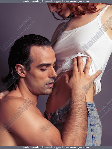 Sensual photo of a young man taking off woman's shirt about to kiss her stomach
