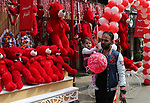 A Palestinian man walks past a shop selling red teddy bears, red ballons and pillows on Valentine's day in Gaza city on February 14, 2018. Valentine's Day is increasingly popular in the region as people have taken up the custom of giving flowers, cards, chocolates and gifts to sweethearts to celebrate the occasion. Photo by Ashraf Amra