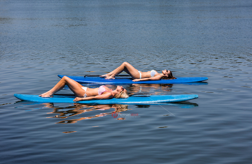 Two sexy young women lay on SUP stand-up paddle boards while sun tanning on Lady Bird Town Lake.