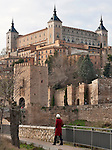 A woman in a red winter coat looks across the Tagus River at the Puente de Alcantara to the old city gate into Toledo, Spain