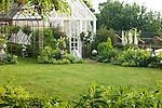 In the early morning light, a small, circular backyard lawn behind the late 19th century farmhouse on this property about an hour north of Seattle is surrounded by a Sissinghurst-style white garden containing white peonies, bleeding heart, delphiniums, white iris, white roses, and garden flox, among others.  The white-painted greenhouse was salvaged from a local arboretum and restored for use here, and adds to the romantic, cottage garden feel. Garden design by Toni Christianson, Christianson's Nursery