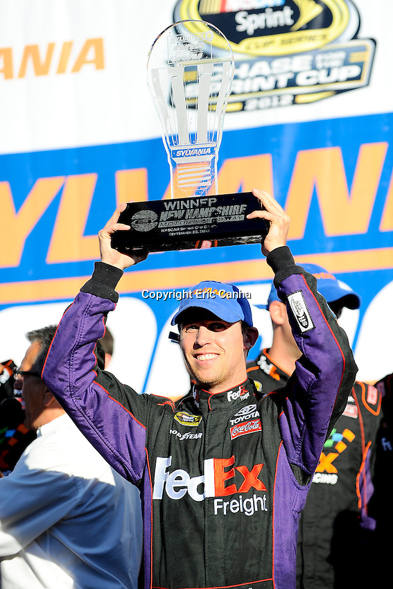 September 23, 2012 Sprint Cup Series driver Denny Hamlin (11) hoists NASCAR Sprint Cup Series Sylvania 300  Winners Trophy  at the New Hampshire Motor Speedway in Loudon, New Hampshire.  Eric Canha/CSM