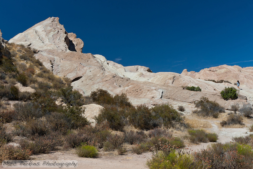 A woman climbs the primary peak of Vasquez Rocks, an unusual formation of rocks in Los Angeles County that's been featured in many films and TV shows (including Star Trek!).
