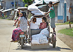 Several people use a motorized tricycle to carry bags of food and other relief supplies home following a distribution of the material to survivors in Estancia, a village in the Philippines that was hit hard by Typhoon Haiyan in November 2013. The storm was known locally as Yolanda. The food items were provided by the National Council of Churches of the Philippines, a member of the ACT Alliance.