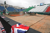employees covering the field because the rain stops the beginning of the quarter-finals of the Davis Cup  tennis match between Italy and Great Britain in Naples April 4, 2014.