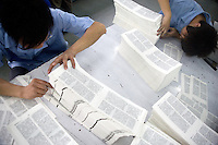 "Amity Printing Company employees check the quality of printed Bible pages in the Amity Printing Company's new printing facility in Nanjing, China....On May 18, 2008, the Amity Printing Company in Nanjing, Jiangsu Province, China, inaugurated its new printing facility in southern Nanjing.  The facility doubles the printing capacity of the company, now up to 12 million Bibles produced in a year, making Amity Printing Company the largest producer of Bibles in the world.  The company, in cooperation with the international organization the United Bible Societies, produces Bibles for both domestic Chinese use and international distribution.  The company's Bibles are printed in Chinese and many other languages.  Within China, the Bibles are distributed both to registered and unregistered Christians who worship in illegal ""house churches."""