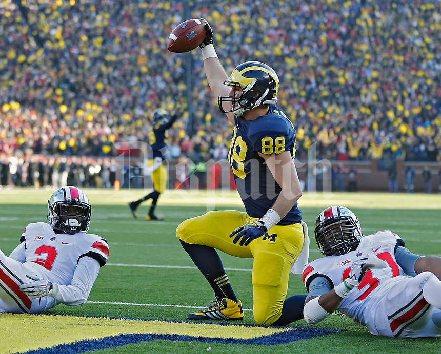 Michigan Wolverines tight end Jake Butt (88) celebrates a touchdown catch against Ohio State Buckeyes defensive back Corey Brown (3) and Ohio State Buckeyes linebacker Joshua Perry (37) in the 4th quarter of their college football game at Michigan Stadium in Ann Arbor, Michigan on November 30, 2013.  (Dispatch photo by Kyle Robertson)