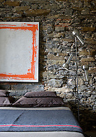 The natural stone wall provides a backdrop for the modern art and simple furnishings of this bedroom