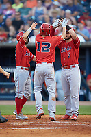 Nick Senzel (12) of the Louisville Bats is greeted at home plate by teammates Blake Trahan (left) and Joe Hudson (right) after hitting a 3-run home run against the Toledo Mud Hens at Fifth Third Field on June 16, 2018 in Toledo, Ohio. The Mud Hens defeated the Bats 7-4.  (Brian Westerholt/Four Seam Images)