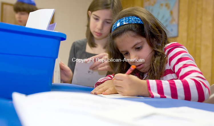 TORRINGTON, CT- 14 DECEMBER 2008 --121408JS01-Lucy Gottfried, 7, of Harwinton, right, and Rebecca Perreault, 12, also of Harwinton, both students at the Beth El Religious School in Torrington, create holiday cards for shut-ins and recovering soldiers at Walter Reed Hospital during the fourth annual Mitzvah Day Sunday at the Beth El Synagogue in Torrington. The event, meaning 'Good Deed' was sponsored by Litchfield County Hadassah. Along with holiday cards and storie books, food and clothing were collected to benefit the Susan B. Anthony Project and FISH food pantry. <br /> Jim Shannon / Republican-American
