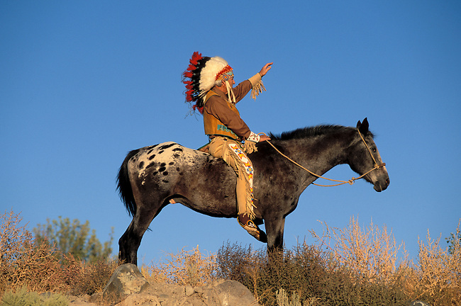 Man dressed in traditional regalia of a feather headdress, leather vest, leggings and breechcloth sits on an Appaloosa, preferred horse of the Nez Perce