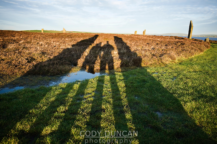 Shadow of two people standing in Ring of Brodgar standing stones, Orkney, Scotland