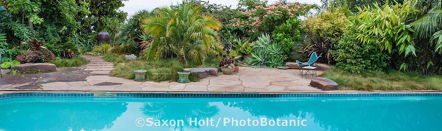 Panorama of Sherry Merciari backyard garden with path through foliage borders, patio, and swimming pool