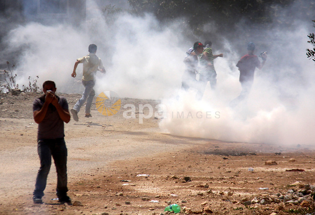 Palestinian demonstrators run as Israeli forces start to fire tear gas during clashes following a protest against the closure of a road during the second Intifada by Jewish settlers from the nearby settlement of Kadumim on August 19, 2011 in the West Bank village of Kfar Kadum. Photo by Wagdi Eshtayah
