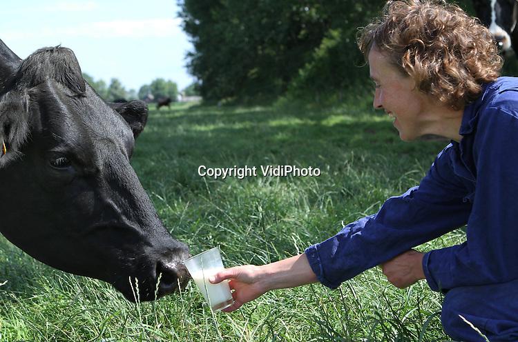 Foto: VidiPhoto..KEKERDOM - De koeien van Herman en Rita Scholtens uit het Gelderse Kekerdom krijgen donderdag een glas melk aangeboden, een bijzondere vorm van recycling. Agrariërs en telers in de Millingerwaard voeren op dit moment tal van acties om hun producten onder de aandacht van de Nederlandse consument te brengen. Ze willen hiermee duidelijk maken dat producten van eigen bodem verser en gezonder zijn dan uit het buitenland. .